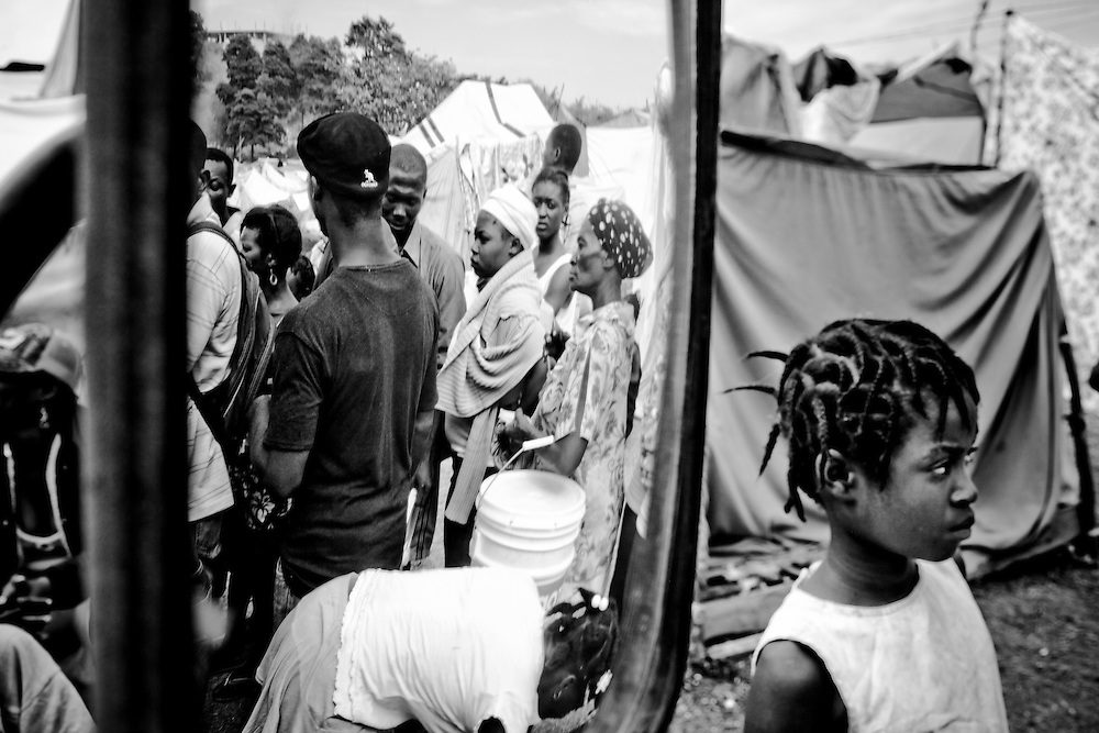 A girl watches people waiting in line to fill buckets with clean water from a truck delivering it to a camp for those displaced by the recent earthquake in Petionville, outside Port-au-Prince, Haiti.