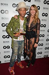 PHARRELL WILLIAMS winner of the Solo Artist Award and CARA DELEVINGNE at the GQ Men Of The Year 2014 Awards in association with Hugo Boss held at The Royal Opera House, London on 2nd September 2014.