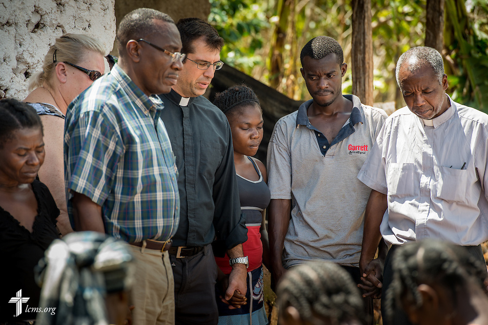 The Rev. Ross Johnson, director of LCMS Disaster Response, prays with residents on Wednesday, Oct. 12, 2016, at a home in Duchity, Haiti. LCMS Communications/Erik M. Lunsford