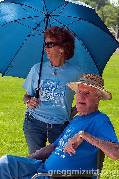 Lawana Johnson provides shade for her neighbor Rolanz Tenne during the Idaho Senior Games at Ann Morrison Park in Boise, Idaho on August 16, 2014.