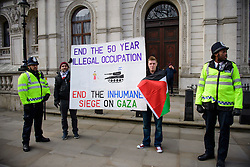 © Licensed to London News Pictures. 06/02/2017. London, UK. Two men hold a banner next to police during as Anti Israeli, pro Palestine demonstration at the gates to Downing Street in London at the time of a meeting between Israeli Prime Minister Benjamin Netanyahu and British Prime Minister Theresa May in Downing Street. Photo credit: Ben Cawthra/LNP