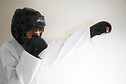 Young Caucasian boy wearing white karate costume and black sparring mitts against white wall background
