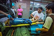 "30 NOVEMBER 2012 - BANGKOK, THAILAND: Volunteer medics with the Ruamkatanyu Foundation unload a woman who collapsed on a Bangkok street from their ambulance at Police General Hospital in Bangkok during a Friday night shift. The Ruamkatanyu Foundation was started more than 60 years ago as a charitable organisation that collected the dead and transported them to the nearest facility. Crews sometimes found that the person they had been called to collect wasn't dead, and they were called upon to provide emergency medical care. That's how the foundation medical and rescue service was started. The foundation has 7,000 volunteers nationwide and along with the larger Poh Teck Tung Foundation, is one of the two largest rescue services in the country. The volunteer crews were once dubbed Bangkok's ""Body Snatchers"" but they do much more than that now.     PHOTO BY JACK KURTZ"