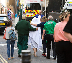 © London News Pictures. 09/08/2013. London, UK. Katie Gee (centre) covered in a white sheet being taken into Chelsea and Westminster Hospital followed by her mother Nicky Gee (far left) after arriving back in the UK. Katie Gee and her friend Kirstie Trup were victims of an acid attack while working as charity volunteers in in Zanzibar. Photo credit : Ben Cawthra/LNP