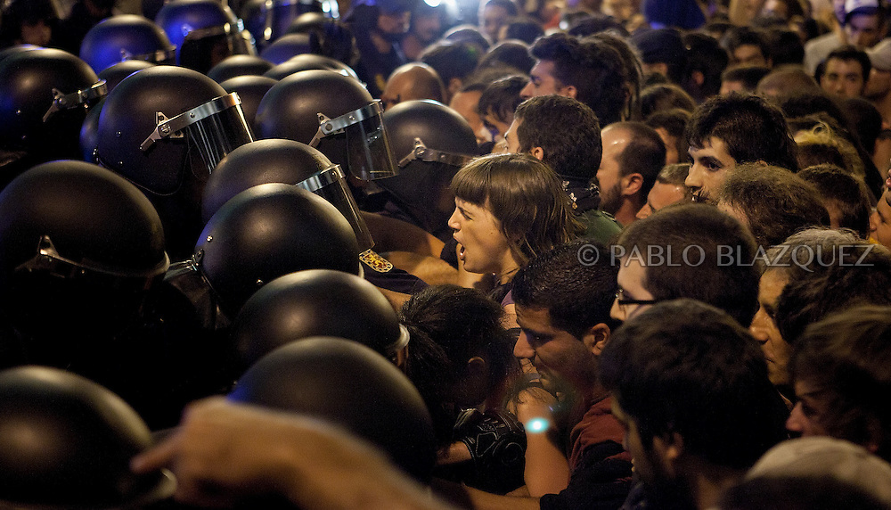 Spanish riot police grapple with 'indignant' protesters who try to gain access to Puerta del Sol Square in Madrid on August 3, 2011, after being evicted in a dawn raid. Hundreds of protesters crammed into each of the sidestreets leading to the central square of Puerta del Sol, birthplace of a nationwide protest against the suffering caused by Spain's economic blight. Lines of riot police crossed their arms and stood in front of the demonstrators, who gathered in swelling numbers in response to Facebook and Twitter pleas for a mass response to their eviction.