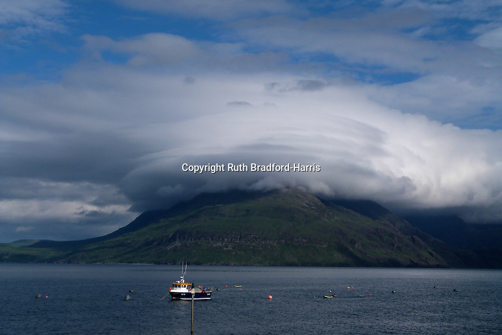 Spectacular lenticular clouds sit like an elaborate hat over the Cuillin peak of Gars-bheinn, photographed from Port Elgol, Isle of Skye. Gars-bheinn is the southern-most peak of the Cuillin Ridge, sometimes referred to as the Black Cuillin because of the dark grey colour of the Gabbro rock of which they consist.<br />
