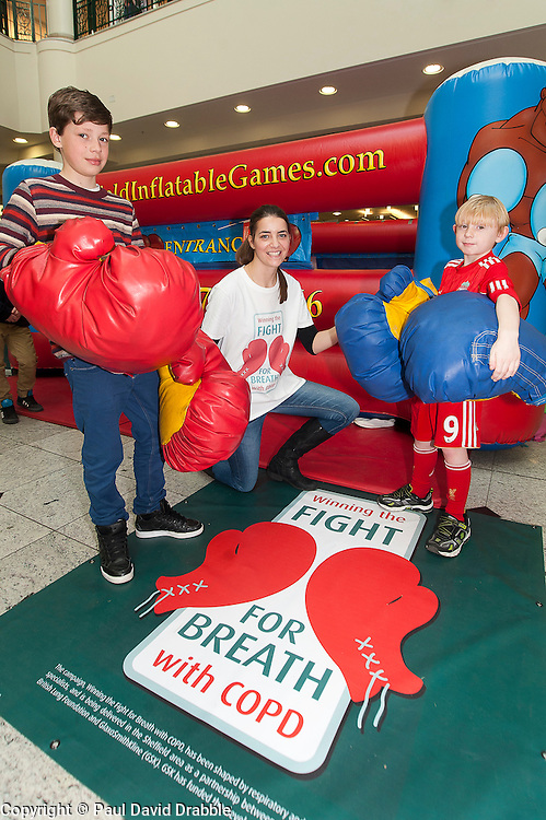"Henry Wallis and Ben Mathison helped into thier boxing gloves by Jessica Law.at the launch of the ""Winning The Fight For Breath  with COPD Campaign"" in Meadowhall Shopping Centre Sheffield on Saturday 18th February 2012..www.pauldaviddrabble.co.uk..18th February 2012 -  Image © Paul David Drabble"