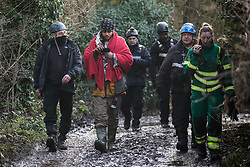 Harefield, UK. 16 January, 2020. Enforcement agents accompany Stop HS2 activist Freeman as he is evicted from the Harvil Road wildlife protection camp in the Colne Valley after over two days and two nights taking refuge in a tree in woodland. 108 ancient woodlands are set to be destroyed by the high-speed rail link and further destruction of trees for HS2 in the Harvil Road area is believed to be imminent.