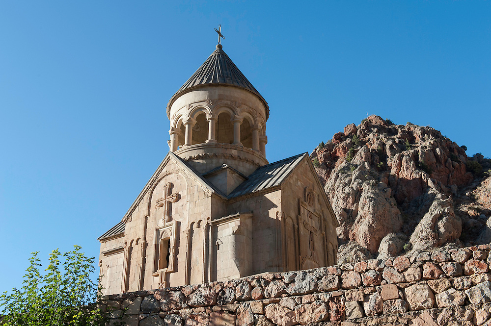"""Noravank, meaning """"New Monastery"""" in Armenian is a 13th-century Armenian monastery, located 122km from Yerevan in a narrow gorge made by the Amaghu river, near the city of Yeghegnadzor, Armenia. The gorge is known for its tall, sheer, brick-red cliffs, directly across from the monastery. The monastery is best known for its two-storey Surp Astvatsatsin Holy Mother of God church, which grants access to the second floor by way of a narrow stone-made staircase jutting out from the face of building. The monastery is sometimes called Noravank at Amaghu, with Amaghu being the name of a small and nowadays abandoned village above the canyon, in order to distinguish it from Bgheno-Noravank, near Goris. In the 13th–14th centuries the monastery became a residence of Syunik's bishops and, consequently. a major religious and, later, cultural center of Armenia closely connected with many of the local seats of learning, especially with Gladzor's famed university and library."""