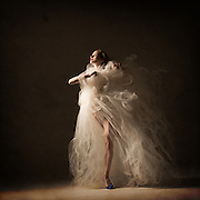 Classical ballet ballerina, Darrah Brewster, with a flowy white tutu. Taken in the photo studio on a black background. Photograph taken in New York City by photographer Rachel Neville.