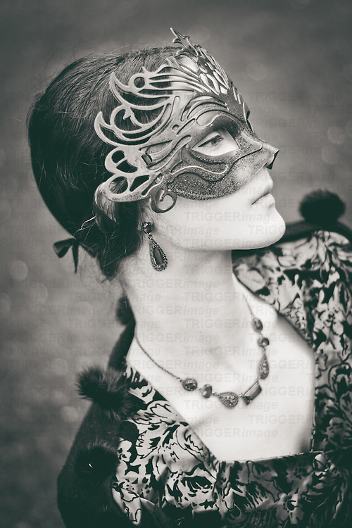 Profile of victorian girl wearing carnival mask, looking down with sad emotion. Monochrome shot.