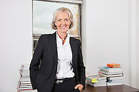 Portrait of smiling senior businesswoman with stack of books on desk in office