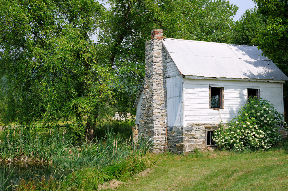 A very old white cottage sitting empty in greenery around a quiet farm pond, a rustic summer scene in the country.
