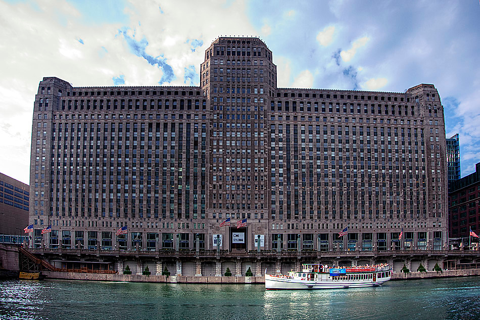 A tour boat passes below the famous Merchandise Mart building in Chicago, IL.