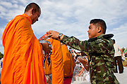 "Sept. 26, 2009 -- PATTANI, THAILAND:  A Thai soldier donates food to a Buddhist monk during the Tak Bat Sankatan ceremony in Pattani, Thailand, Saturday. Buddhists in Thailand's three southern most provinces gathered in Pattani Saturday, Sept 26 to celebrate Tak Bat Sankatan, the day Lord Buddha returned to earth and was greeted by a crawd of his disciples and Buddhist believers who were waiting to offer him food. Buddhists monks representing the 266 ""Wats"" (temples) in the three provinces (Pattani, Narathiwat and Yala) processed through the crowd and were presented with food and gifts.   Photo by Jack Kurtz"