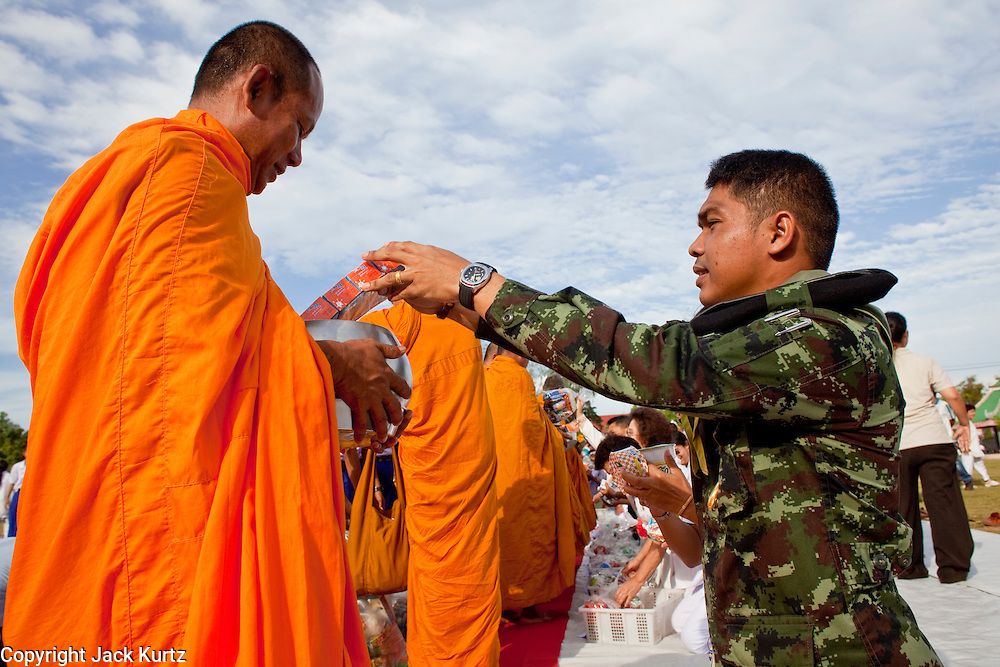 """Sept. 26, 2009 -- PATTANI, THAILAND:  A Thai soldier donates food to a Buddhist monk during the Tak Bat Sankatan ceremony in Pattani, Thailand, Saturday. Buddhists in Thailand's three southern most provinces gathered in Pattani Saturday, Sept 26 to celebrate Tak Bat Sankatan, the day Lord Buddha returned to earth and was greeted by a crawd of his disciples and Buddhist believers who were waiting to offer him food. Buddhists monks representing the 266 """"Wats"""" (temples) in the three provinces (Pattani, Narathiwat and Yala) processed through the crowd and were presented with food and gifts.   Photo by Jack Kurtz"""