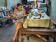 30 DECEMBER 2015 - BANGKOK, THAILAND:   A woman drinks an instant coffee from a coffee stand on the street in front of Bang Chak Market. The market is supposed to close permanently on Dec 31, 2015. The Bang Chak Market serves the community around Sois 91-97 on Sukhumvit Road in the Bangkok suburbs. About half of the market has been torn down. Bangkok city authorities put up notices in late November that the market would be closed by January 1, 2016 and redevelopment would start shortly after that. Market vendors said condominiums are being built on the land.           PHOTO BY JACK KURTZ