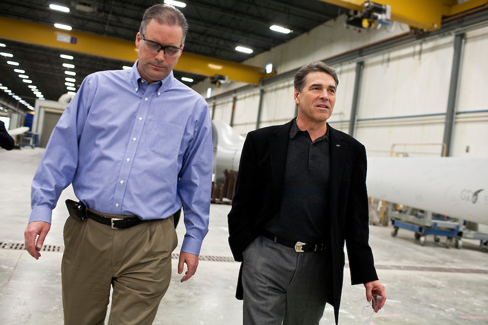 Republican presidential candidate Rick Perry, right, arrives to speak at an employee town hall at TPI Composites on Thursday, December 22, 2011 in Newton, IA.
