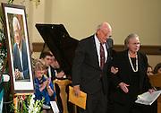 Judge Justin Quackenbush escorts Mrs. Heather Foley, wife of House Speaker Thomas Foley, from the stage during the memorial for the legendary leader Nov. 1, 2013 at St. Aloysius Church. (Photo courtesy of Gonzaga University)