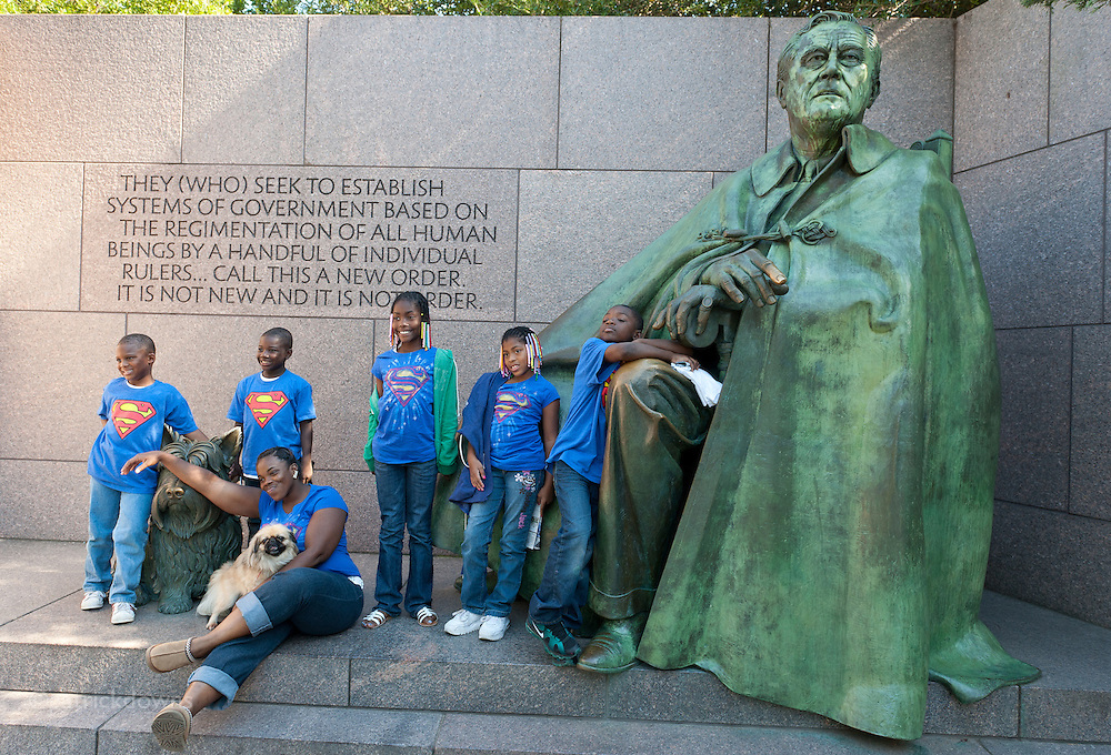 A family poses for a portrait in front of the statue of Franklin D. Roosevelt, at the memorial dedicated to him in Washington DC.