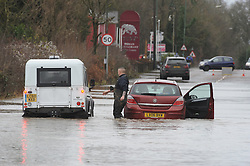 © Licensed to London News Pictures. 24/12/2013<br /> Men attending to abandoned car after helping an ambulance.<br /> London Road A224  Polhill in Halstead, Kent is closed with cars abandoned in 4 feet of rain water overnight.<br /> The UK  has woken up to trees and electricity cables down following a night of gale-force winds and torrential rain.<br /> Photo credit :Grant Falvey/LNP