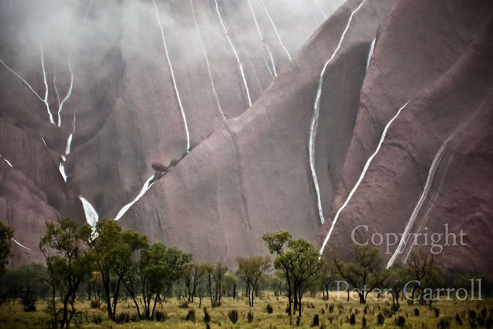 14 Oct 2010. Water pours down the flanks of Uluru near Mutitjulu Waterhole after heavy rain overnight.