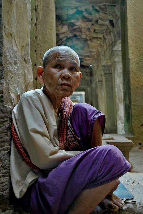This Cambodian woman was meditating in one of the many corridors of an interior building in the Angkor Wat temple complex which was built for King Suryavarman II in the early 12th century as his state temple and capital city. <br /> <br /> It is a massive three-tiered pyramid crowned by five lotus-like towers rising 65 meters from ground level is surrounded by a moat and an exterior wall. All the walls of the temple are covered inside and out with bas-reliefs and carvings including nearly 2000 apsara carvings representing some of the finest examples of apsara carvings in Angkorian era art.<br /> <br /> The ruins of Angkor, a UNESCO World Heritage Site with temples numbering over 1000, are hidden amongst forests and farmland to the north of the Tonle Sap Lake outside the modern city of Siem Reap, Cambodia. <br /> <br /> Quite a few of the temples at Angkor have been restored and represent a significant site of Khmer architecture.