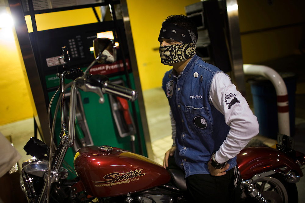 A young man fills up his motorcycle at a gas station in Culiacan, Mexico. Ostentatious displays of wealth, like this motorcycle, are a large part of Mexico's Narco Culture.