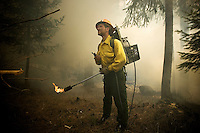 JEROME A. POLLOS/Press..Josh Jenquine, a firefighter with MAWB Wildland Management, watches a hillside in a Hayden residential neighborhood while he awaits further instructions on which slash piles to burn Tuesday. The crew was clearing brush and other debris for fire prevention under the FireSmart program. Smoke will continue today as additional slash piles are cleared near Loch Haven Drive and Prairie Avenue.