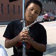 Nederland Rotterdam 24-05-2009 20090524 Foto: David Rozing .                                                                                    .Achterstandswijk Bloemhof Rotterdam Zuid, jongen met speelgoed step en pistool.   Young boy showing off his toy gun. PLAATSING IN OVERLEG .Foto: David Rozing