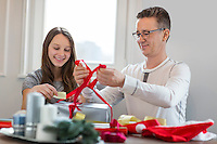 Smiling father and daughter wrapping Christmas present at home