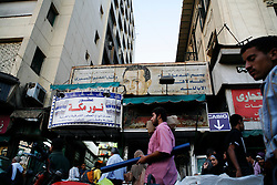 Street vendors in Cairo walk in front of a sign of Egyptian President Hosni Mubarak.