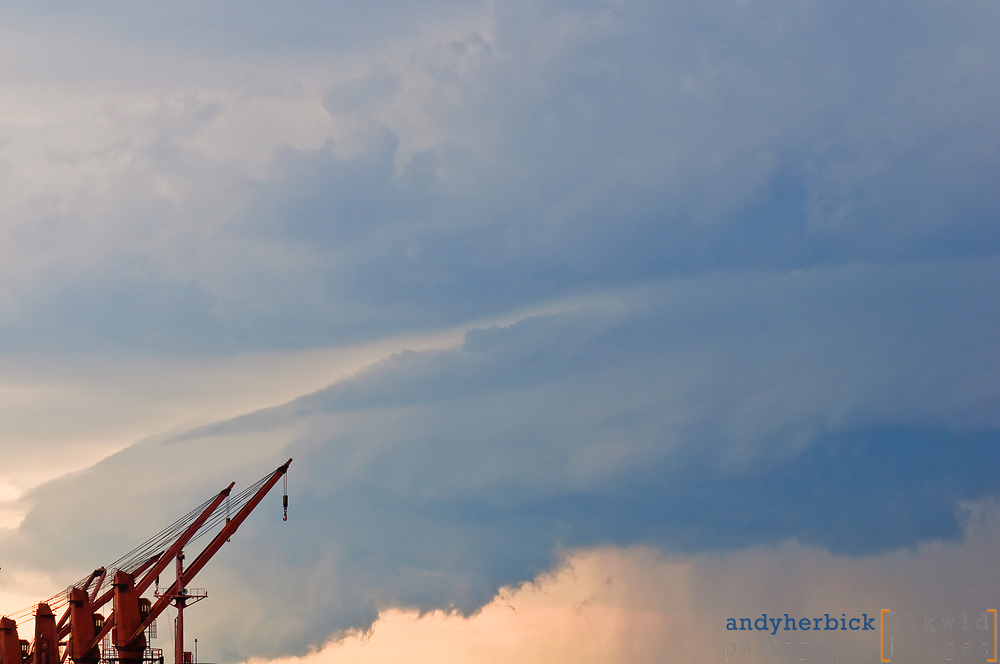 "Deck cranes of the cargo ship ""Lucky Transporter"" under the dark clouds of summer storm"