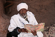 An Ethiopian Orthodox Christian priest reads outside a rock-hewn church in Lalibela. Located at 2,500 meters above sea level, Lalibela is one of Ethiopia's holiest cities and a center of pilgrimage for the Ethiopian Orthodox Christian population. Declared a UNESCO World Heritage Site, Lalibela's rock-hewn churches were built in the 12th and 13th centuries and are said to represent a miniature version of Jerusalem. Lalibela, Amhara Division, Ethiopia. March 31, 2011.