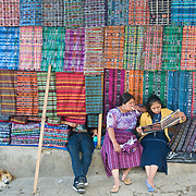 A family sells textiles in the market of San Pedro. The different Mayan groups around the lake and elsewhere dress in distinct outfits and designs for their cultural group.   San Pedro la Laguna, Lago de Atitlan, Guatemala.  (Photo/William Byrne Drumm)