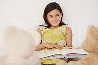 Girl reading story to teddy bears sitting on bed