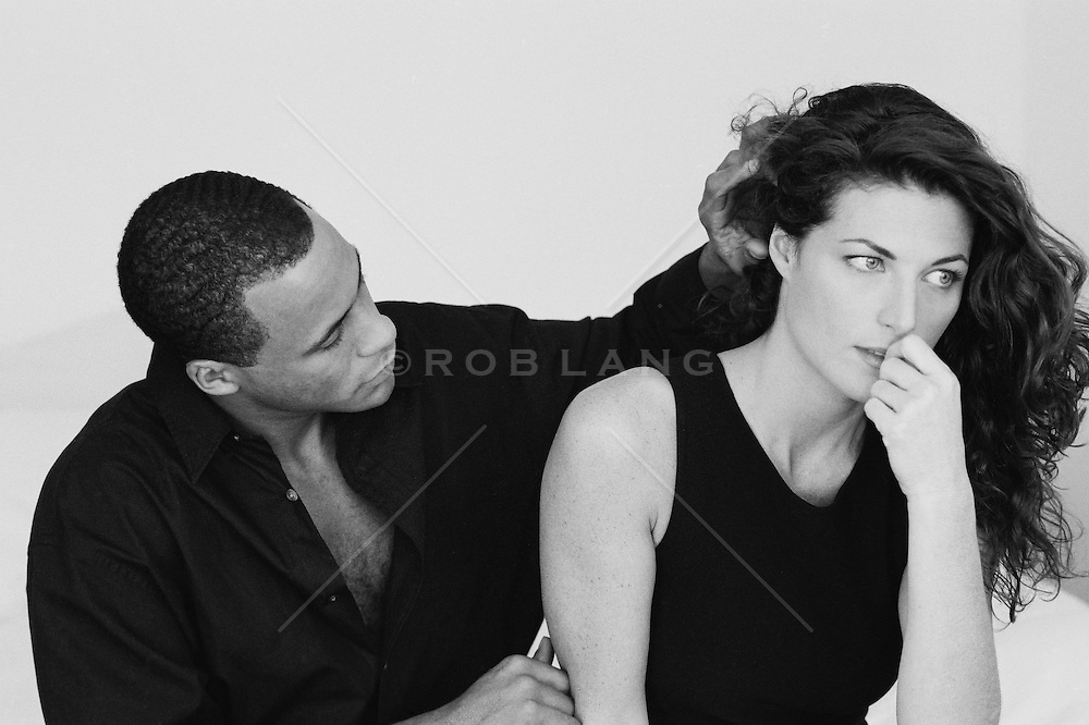 African American man comforting Caucasian Woman in Deep Thought