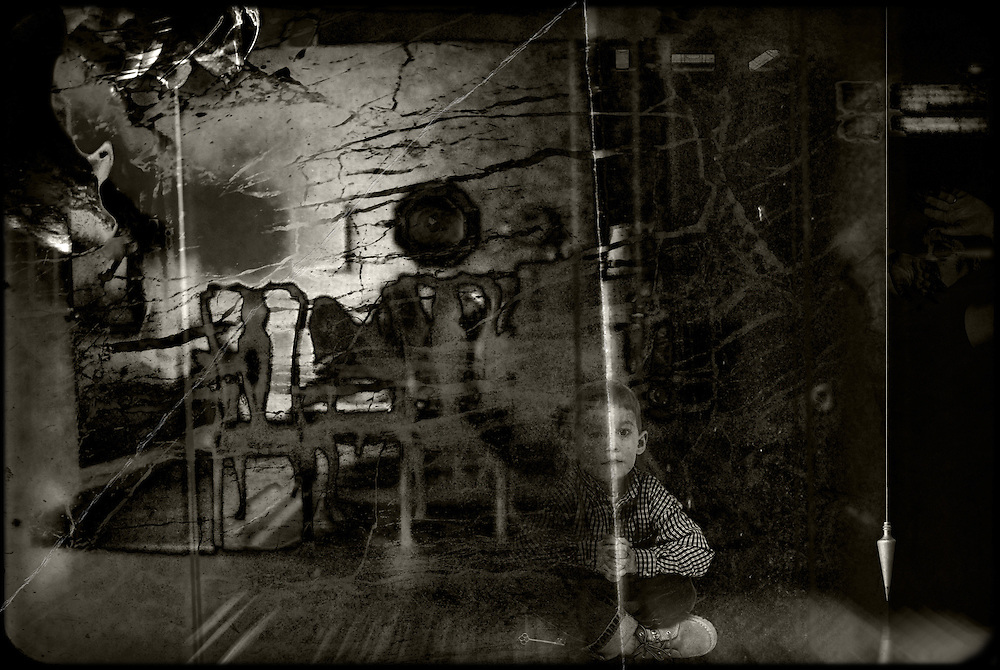 A child sits in a haunted room, caught between one reality and the next.