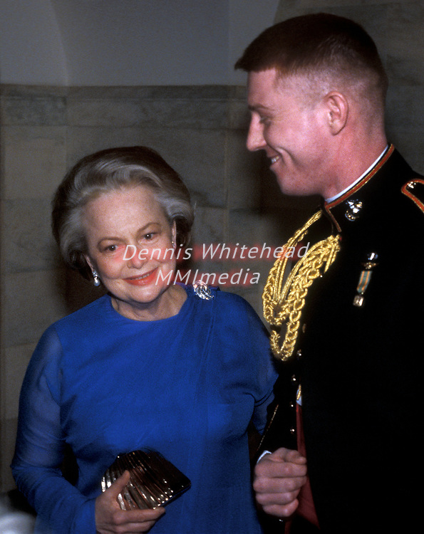 Actress Olivia de Havilland is escorted by an unknown Marine at the White House on February 28, 1984.