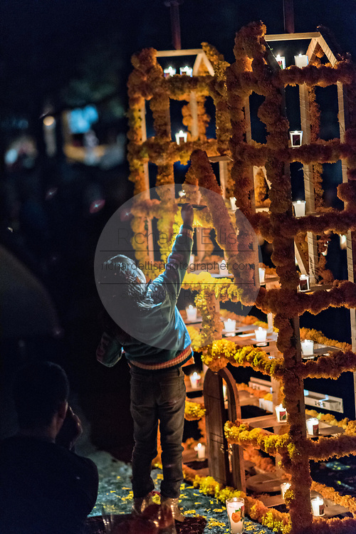 A young girl lights candles around the gravesite of a family member during the Day of the Dead festival October 31, 2017 in Tzintzuntzan, Michoacan, Mexico.