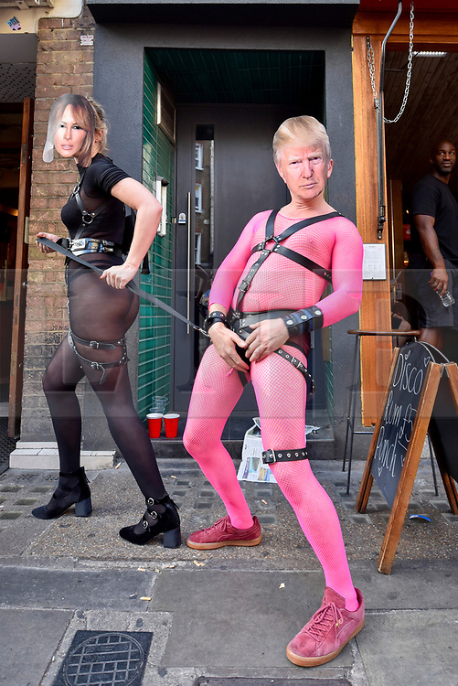 © Licensed to London News Pictures. 08/07/2017. London, UK. A couple in bondage gear dressed as Melania and Donald Trump celebrate. Thousands of people enjoy the Pride Festival in Soho's Old Compton Street following the annual Pride in London Parade, the largest celebration of the LGBT+ community in the UK.   Photo credit : Stephen Chung/LNP