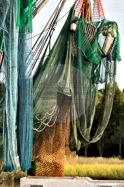 Nets hang from the boom on a shrimp boat along Jeremy Creek in the village of McClellanville, South Carolina.
