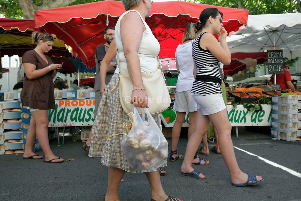 woman with fresh garlic at  an outdoors regional farmers market