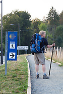 Male pilgrim standing near the Camino sign, on the French Route of the Camino de Santiago de Compostela, with the mile/kilometer marker in the background.