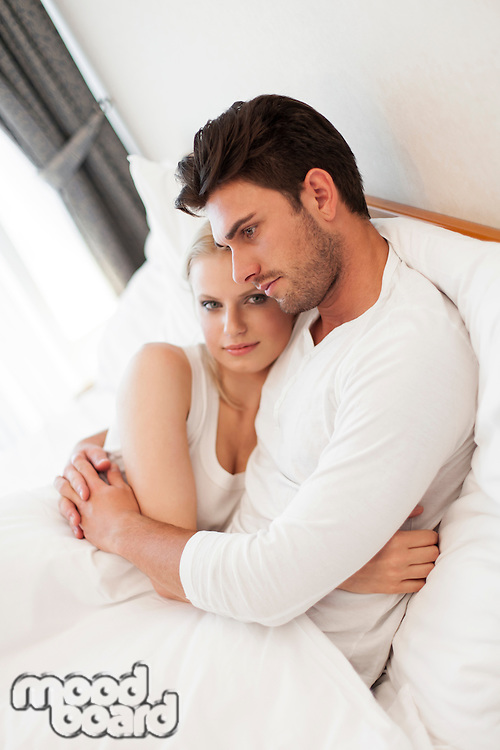 Portrait of young woman with man embracing in hotel room
