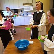 Nuns at Our Lady of the Mississippi Abbey,  a monastery of Trappist nuns, share a light moment while finishing off the popcorn in their candy factory break room.  The occasion was a 50th birthday celebration for Sister Ciaran Sheilds, right.  Joining in the fun are Sisters Kathleen O'Neill, left, and Carol Dvorak.    The community of 22 Roman Catholic women follow Jesus Christ through a life of prayer, silence, simplicity and ordinary work.  Their home is a beautiful monastery which sits high on a bluff, overlooking the Mississippi River.