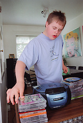 Teenage boy with Downs Syndrome with collection of compact disks,