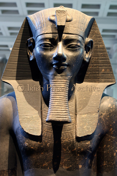 Statue of king Amenhotep III. 18th Dynasty, about 1400 BC from Thebes The king is represented in classic pose and dress. Seated on a throne with both hands flat on the knees, her wears a nemes-headcloth, false beard and short kilt, which fitted with a ceremonial bull's tail, shown between the leg. The king's names are inscribed on the front and back of the throne and on the belt of the kilt.