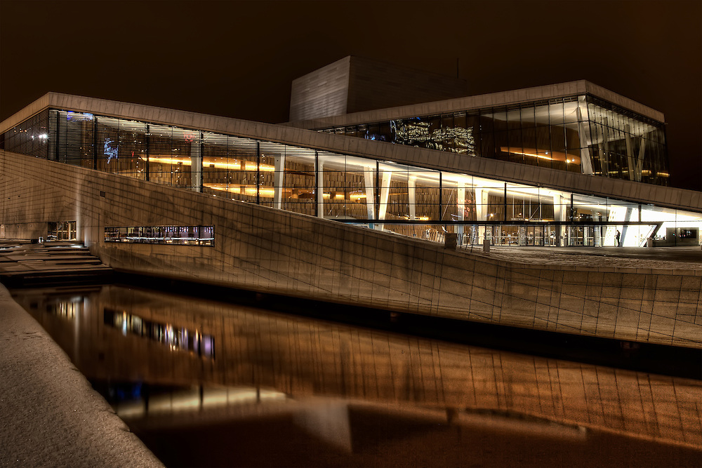 The Oslo Opera House is the home of The Norwegian National Opera and Ballet, and the national opera theatre in Norway. The building is situated in the Bjørvika neighbourhood of central Oslo, at the head of the Oslofjord and was designed by the architect Tarald Lundevall. The structure contains 1,100 rooms in a total area of 38,500 m2 (414,000 sq ft). The main auditorium seats 1,364 and two other performance spaces can seat 200 and 400. The angled exterior surfaces of the building are covered with Italian marble and white granite and make it appear to rise from the water.