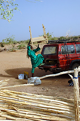 Niger, Agadez, Tidene, 2007. Heishi Ali unloads equipment and provisions for the central storehouse on Tidene land. Well workers use this small market for essentials.